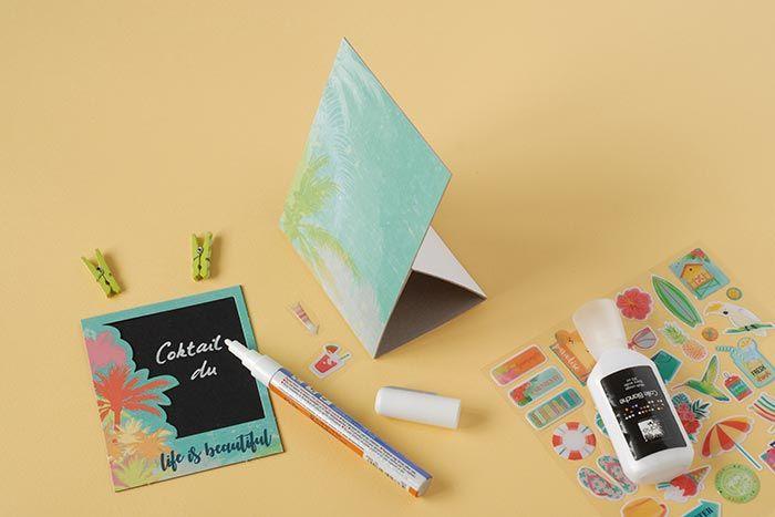 5. Après avoir découpé dans la feuille ardoise : 1 x (8,5 x 8,5 cm). Choisir un polaroïd. Coller la feuille ardoise au dos du polaroïd. A l'aide d'un stylo craie, écrire  «Cocktail du jour». Décorer avec les stickers. Plier le support au niveau des pointillés.