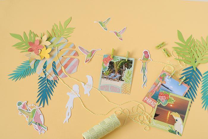 8. Coller les feuilles et les fleurs entre elles. Couper la ficelle aux dimensions voulues et la coller au dos des fleurs. Coller les oiseaux sur la ficelle et suspendre les photos à l'aide de mini pinces.