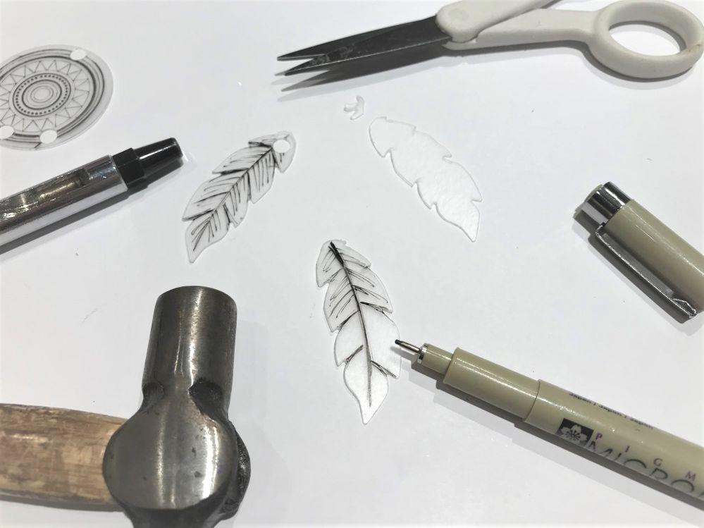 Avec un stylo encre dessiner les motifs plumes, couper les extrémités pour les arrondir et les perforer avec l'outil pour oeillets