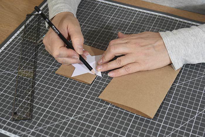 ETAPE 2/8 Positionner au choix sur une petite carte le gabarit étoile, maison ou petit sapin en veillant à déborder le gabarit de quelques millimètres sur le côté gauche, au niveau du pli de la carte. Marquer les repères avec un crayon et découper en suivant les repères. Répéter cette action pour les 4 grandes cartes restantes avec le gabarit « grand sapin ».