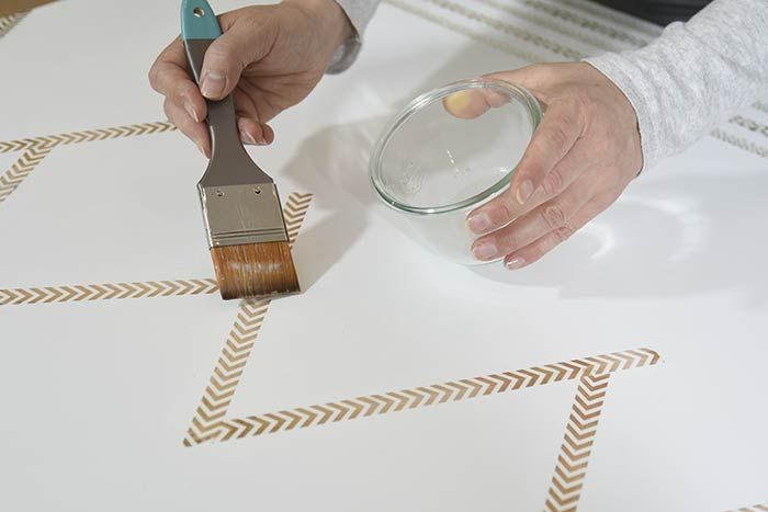 ETAPE 6/8 Télécharger le schéma de fond de toile et coller sur la toile blanche des masking tapes pour former un décor semblable.  Conseil : Pour assurer une meilleure tenue des masking tapes, enduire la toile d'une couche de vernis avant de les coller puis repasser une couche de vernis par dessus. Laisser sécher.