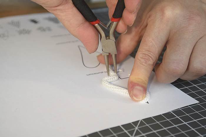 ETAPE 2/14 Télécharger et imprimer le gabarit des motifs sur cultura.com. Placer le fil tricotin sur le motif choisi et suivre les contours avec le fil tricotin pour lui donner forme. Conseil : S'aider d'une pince à bijoux pour manier le fil et fermer la forme.