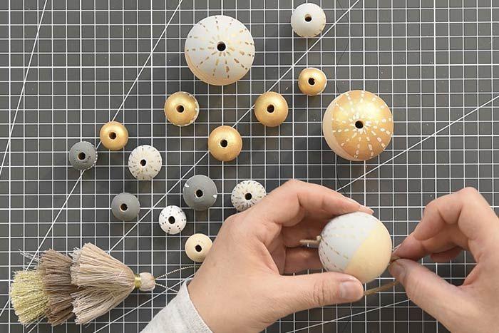 ETAPE 11/14 Couper une longueur de suédine de 30 à 40 cm, insérer au centre un triple pompon puis glisser une perle en bois décorée de 50 mm et une plus petite perle dans les deux longueurs. Nouer pour créer une boucle en guise de suspension.