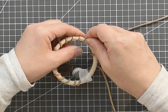 ETAPE 12/14 Anneaux pompons Couper une longueur de 90 cm, coller une extrémité sur l'anneau en bois et laisser sécher quelques secondes. Enrouler la suédine sur l'anneau bois puis l'enfiler dans une perle décorée et dans l'anneau du long pompon.