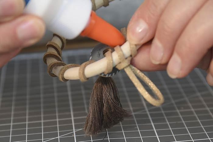 ETAPE 13/14 Repasser la suédine dans la perle décorée puis former une boucle pour créer la suspension et nouer autour. Couper l'excédent de suédine et le coller.