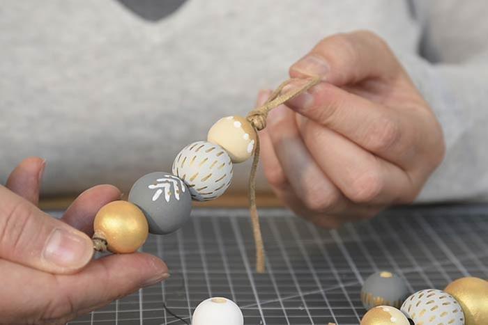 ETAPE 14/14 Suspensions perlées Couper une longueur de suédine de 30 à 40 cm et nouer une extrémité. Insérer 3 à 4 perles décorées en variant leurs tailles et leurs couleurs. Créer une boucle avec la suédine pour former une suspension.
