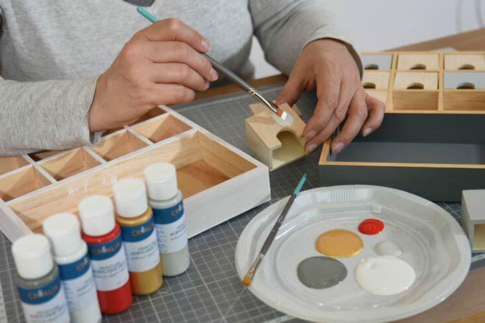 Peinture du calendrier Passer une sous-couche de gesso sur le support et les tiroirs. Laisser sécher. Peindre en blanc la face avant du support. Peindre en gris souris la face arrière, les tranches extérieures et l'intérieur des deux grands casiers. Peindre les tranches intérieures en doré. Pour créer un coloris gris clair, mélanger 1/5 de ficelle, 1/5 de gris souris et 3/5 de blanc. Peindre 8 tiroirs en blanc, 8 tiroirs en gris clair et les 8 derniers en rouge. Laisser sécher.  