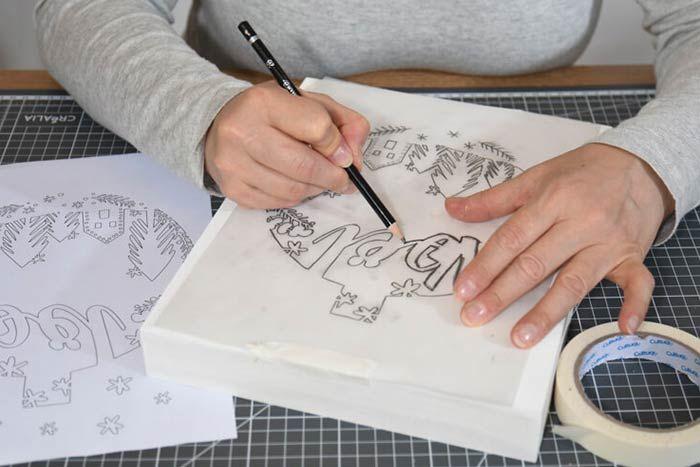 Décoration de l'extérieur du calendrier 1. Télécharger et imprimer le gabarit du décor enneigé sur cultura.com. Reproduire le motif par transparence avec un crayon à papier sur le papier calque puis le retourner et le centrer sur la face avant du calendrier. Repasser sur chaque tracé par transparence : le motif se décalque sur le calendrier.