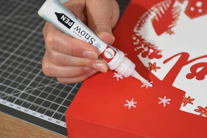 3. Dessiner des étoiles blanches pailletées en relief à l'aide du stylo snow pen mica pour finaliser la décoration. Laisser sécher