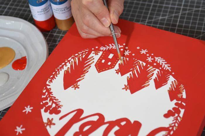 2. Peindre minutieusement en rouge la tranche extérieure de la face avant du calendrier et toute la partie extérieure du motif laissant le décor intérieur blanc. Apporter des petites touches dorées sur les sapins et la maison. Laisser sécher.