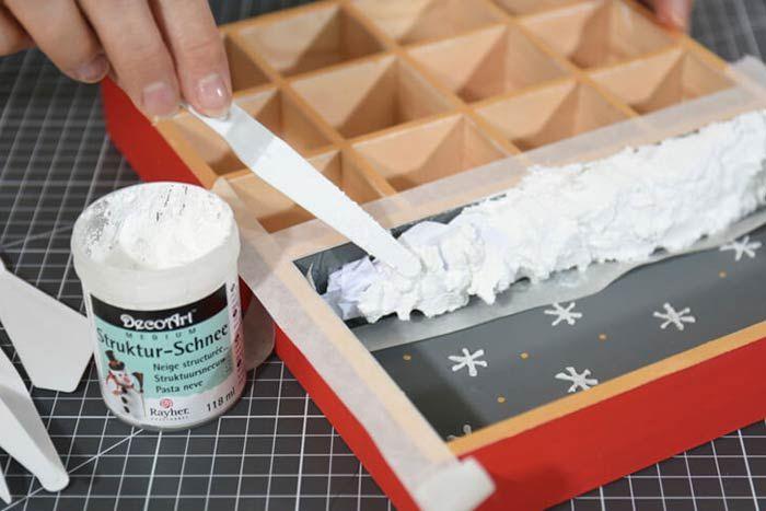 2. Pour créer un effet enneigé, froisser du papier de soie blanc et le coller sur la base du casier puis le recouvrir de neige structurée à l'aide d'un couteau en plastique. 