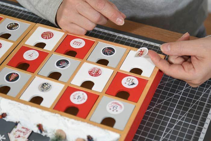 4. Insérer les tiroirs dans les casiers et coller les 24 stickers numéros décoratifs de la collection.  