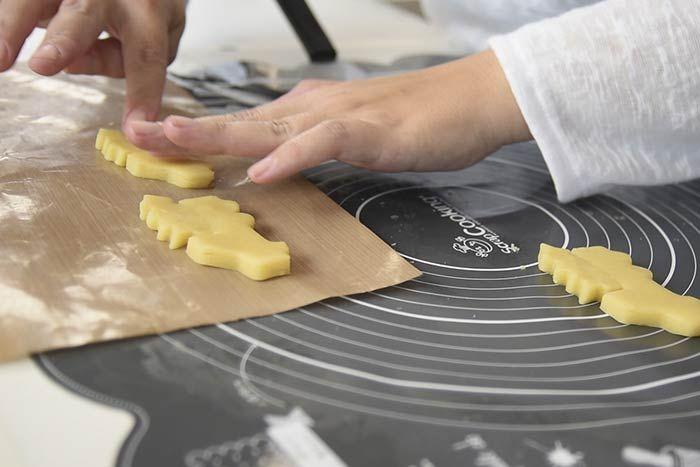 Pour créer le biscuit « sapin dans la camionnette », couper un petit sapin à la verticale sur sa partie droite et le coller sur le dos de la camionnette. Déposer les sablés sur une feuille de cuisson. Enfourner à 180° et cuire 12 minutes. Laisser refroidir. Conseil: Créer 3 à 4 de ces biscuits pour avoir plusieurs bases à travailler lors du glaçage.