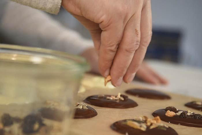 Hacher des fruits secs. Les répartir sur les palets.  Ajouter des fruits secs entiers (Amandes, noix, noisettes et baies de Goji).