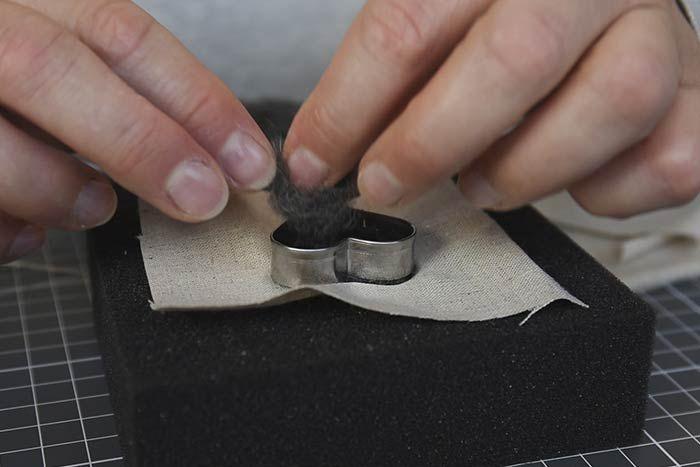 Positionner le petit emporte-pièce étoile ou cœur au centre de la pièce de tissu et insérer la laine feutrée à l'intérieur.