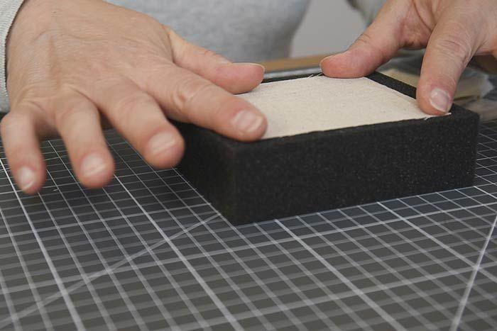Création des motifs en laine feutrée Couper 6 pièces de tissus de 8 x 8 cm. Placer une première pièce sur le carré de mousse.