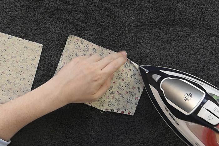 Plier vers l'intérieur les parties A et B indiquées sur le patron. Repasser et coudre à 0,2 cm du bord. Conseil: Repasser le tissu pour former chaque pli.