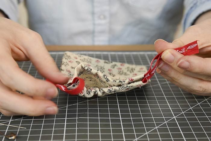 Couper deux longueurs de rubans de 28 cm. Insérer un premier ruban dans une fente du sachet à l'aide d'une épingle à nourrice puis l'insérer dans la seconde fente pour revenir au point de départ. Répéter cette action dans l'autre sens avec le second ruban.