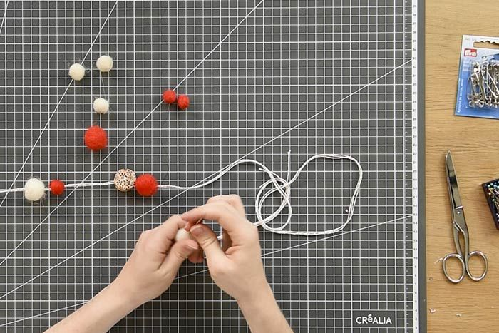 Création de la guirlande de l'Avent Pour créer la base de la guirlande, couper 3 longueurs de ficelle bicolore de 150 cm. Les insérer dans le chas d'une aiguille.