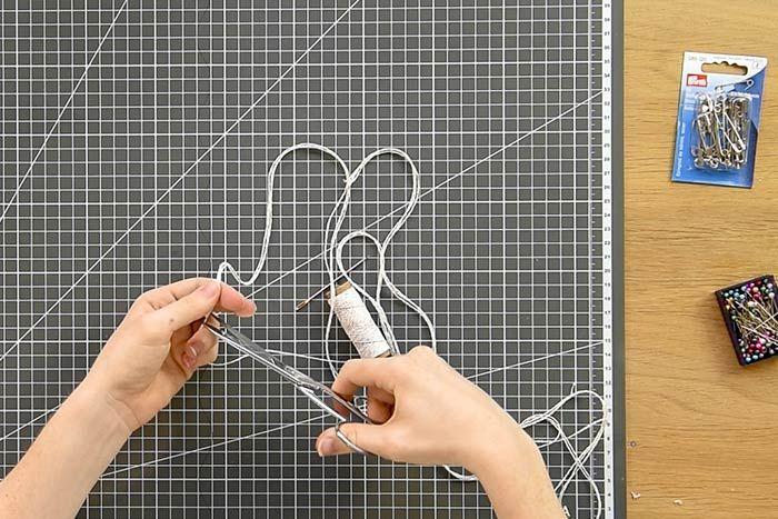 Enfiler des boules de laine feutrée rouge et écrue et des boutons de la collection à l'aide de l'aiguille. Varier les espaces entre chaque accessoires.  Astuce :pour un meilleur maintien des boutons, en enfiler deux dos à dos sur la ficelle. Créer un nœud entre les deux avant de poursuivre la guirlande avec les boules de laine feutrée.