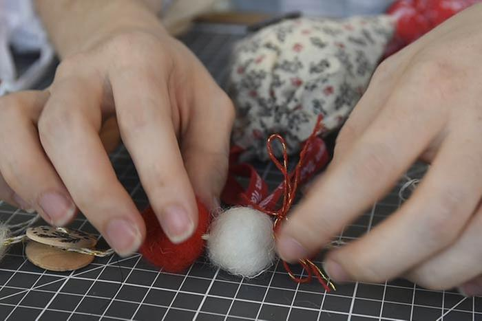 nsérer les surprises dans les 21 sachets en tissu réalisés et dans les 3 sachets de la collection. Les fermer en serrant les rubans. Enfiler une longueur de ficelle dans les anses des sachets et les nouer harmonieusement sur la base de la guirlande.