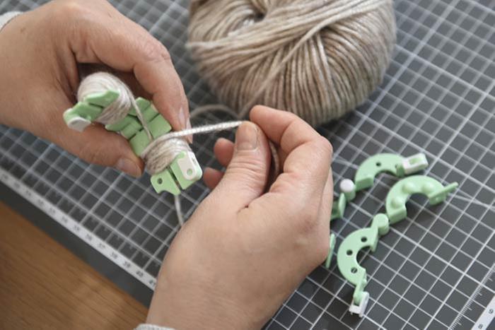 ETAPE 1/8 Création d'un pompon rond 1.Enrouler la laine Metallo sur le gabarit en suivant les instructions ci-dessus. Répéter cette action avec différentes couleurs de laine pour créer d'autres pompons.