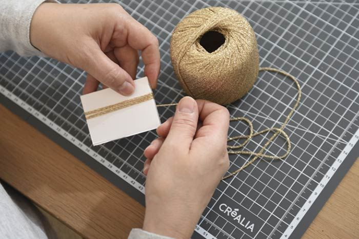 ETAPE 3/8 Création d'un pompon gland 1. Enrouler quarante tours de laine Myriade sur un morceau de carton de 7 cm de hauteur en suivant les instructions ci-dessus.