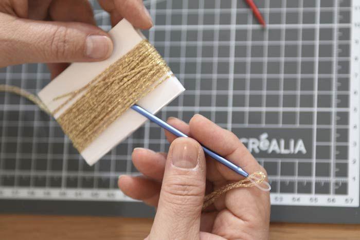ETAPE 4/8 2. Couper 10 cm de laine et l'enfiler dans l'aiguille à laine. Nouer la partie haute entre les brins et le carton. Couper 20 cm de laine et créer le sommet du gland en enroulant de plusieurs tours le brin de laine, à environ 1 cm du premier noeud.
