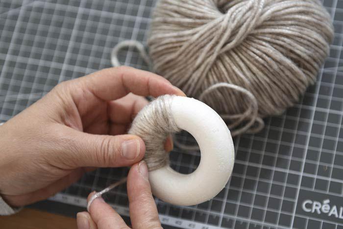 ETAPE 6/8 Création des couronnes 1. Positionner dos à dos 2 mini couronnes en polystyrène. Recouvrir toute la surface d'un couronne en polystyrène de laine Metallo. Couper une longueur de 15 cm de ruban et créer la suspension en collant dos à dos les deux extrémités.