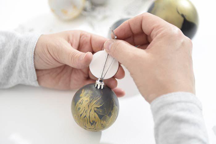 ETAPE 7/7 Décoration des boules Remettre les attaches sur les boules et personnaliser la ficelle en collant un accessoire décoratif à l'aide d'un pistolet à colle.