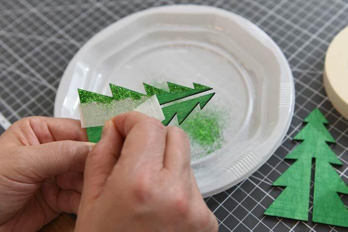 ETAPE 5/8 3. Retirer le ruban de masquage et laisser sécher. Répéter les actions précédentes pour pailleter l'envers de chaque partie du sapin puis le monter en 3 dimensions.