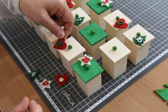 ETAPE 7/8 2. Positionner les tiroirs verts et ceux laissés en bois naturel sur le plan de travail en 3 rangées de 8. Coller un numéro décoratif adhésif en feutrine sur chacun puis insérer les tiroirs dans le calendrier.