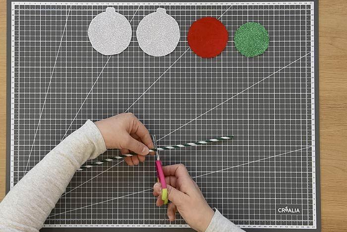 ETAPE 4/8 Couper en deux une longueur de fil chenille. Perforer un petit trou au sommet des deux bases de la boule à l'aide de la pointe d'un stylo bille. 
