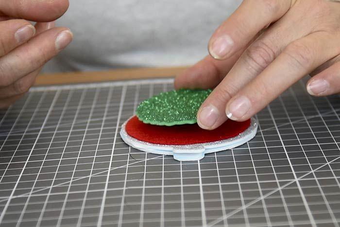 ETAPE 5/8 Coller dos à dos les deux bases ensemble puis superposer et coller les ronds découpés, du plus grand au plus petit, sur la base de la boule à l'aide de la colle textile. 