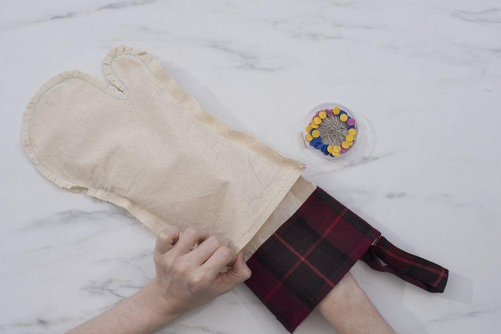 5.Glisser la chaussette tartan dans le gant (ce dernier toujours à l'envers) endroit contre endroit. Placer des épingles sur le haut de la chaussette et du gant, pour les maintenir ensemble.