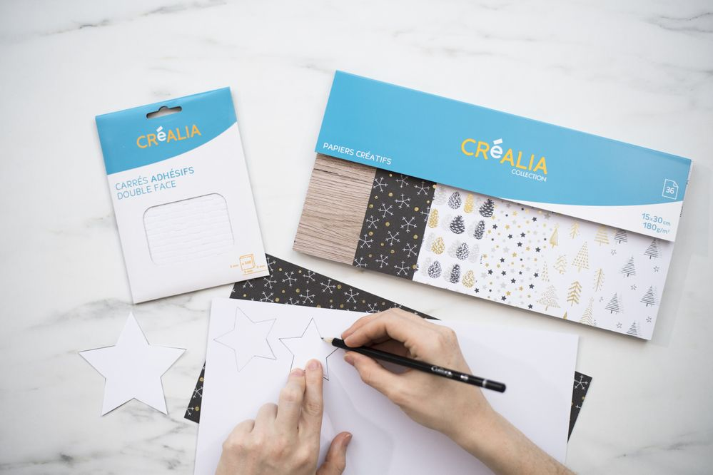 2.A l'aide du crayon tracer deux fois les gabarits des étoiles au dos des papiers de la collection.
