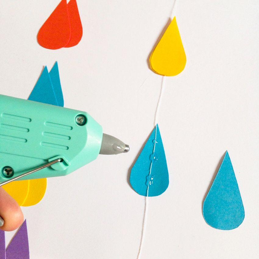 Réalisez vos guirlandes de pluie en découpant des gouttes d'eau dans les feuilles de couleurs, après avoir réalisé un petit gabarit pour qu'elles soient toutes identiques, et collez-les 2 par 2 sur le fil que vous aurez préalablement coupé à la bonne longueur.