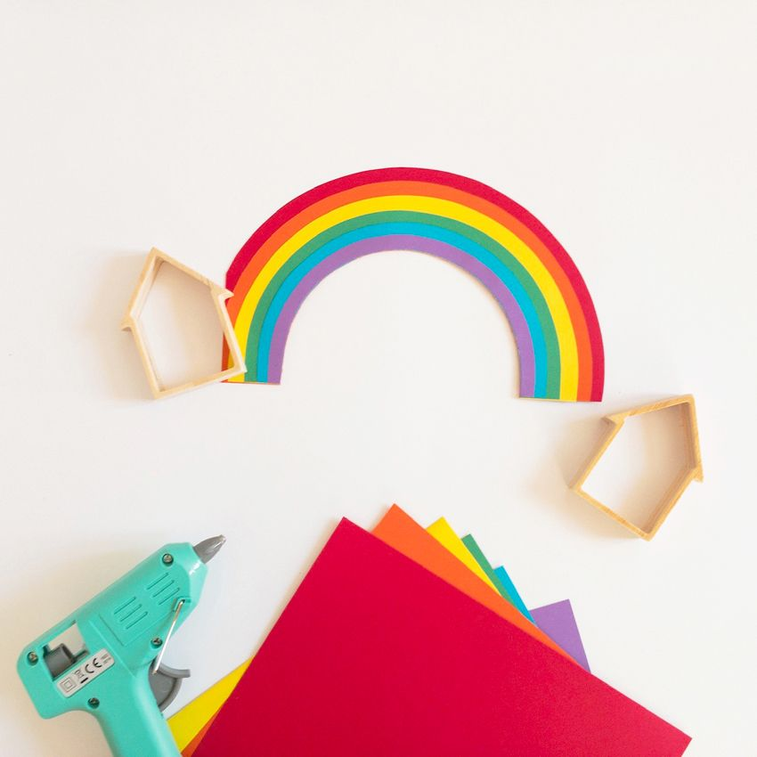 Réalisez ensuite un arc-en-ciel en découpant des bandes de papier couleur que vous collerez les unes aux autres en les superposant ; dans cet exemple, l'arc-enciel fait la largeur d'une maisonnette pour qu'il puisse lui servir de fond.