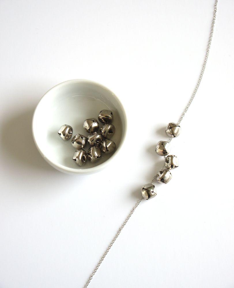 Enfiler les grelots les plus petits suivi des plus gros, en terminant par des plus petits pour avoir un collier bien symétrique. Refermer les anneaux de la chaîne.