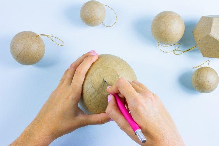 Etape 1 : Pour accueillir les boules vases dans votre sapin il faut y rattacher une ficelle dorée. Pour cela faites un incision du côté fermé de la boule à l'aide d'un cutter afin d'y faire passer le fil doré.