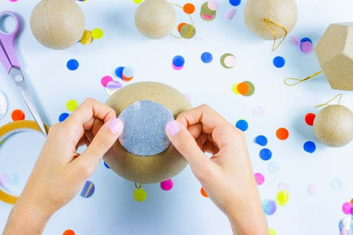 Etape 4 :  Pour que les surprises à l'intérieur de la piñata ne tombent pas, il va falloir reboucher le trou. Découper un rond plus grand que l'ouverture du vase dans un papier crépon argent ou doré. Venez coller le rond sur l'ouverture grâce à du ruban adhésif double faces.