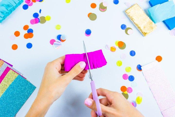 Etape 5 : Maintenant que la boule est préparée et sécurisée, place à votre créativité ! Coupez dans vos papiers crépons, papiers de soie et feuilles glitter des bandes, ni trop fines ni trop larges. Une fois les bandes découpées, venez y découper des franges à tailles égales en laissant une marge non découpée.