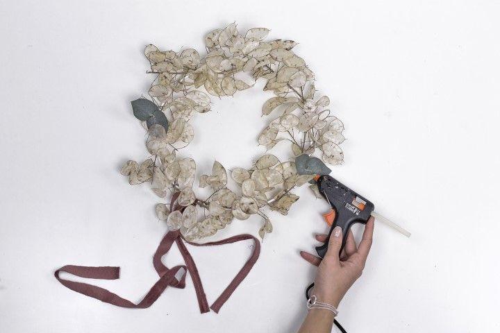 5. Utiliser quelques feuilles d'eucalyptus et les coller au cerceau métallique, afin d'intégrer un peu de verdure dans la couronne.