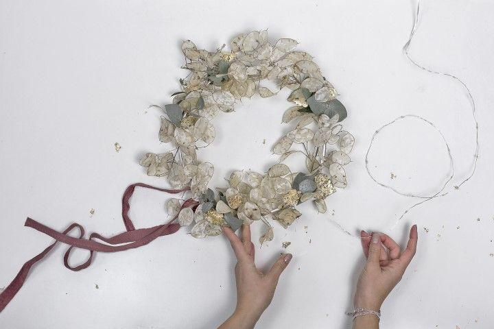 7. Une fois les petites touches d'or posées délicatement sur quelques feuilles, il ne restera plus qu'à faire parcourir la guirlande lumineuse le long du cerceau métallique. Afin d'apporter la touche finale de Noel. Prendre soin d'installer le boitier à piles au haut de la couronne et de le fixer au fil de fer, afin de le rendre plus discret. Vous obtiendrez une couronne de Noel lumineuse à suspendre à sa porte et à illuminer les jours de fêtes.
