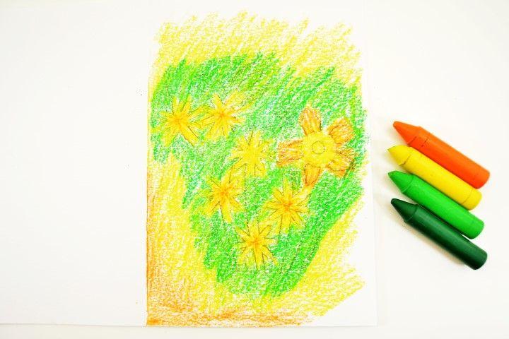 2. Colorer les différentes parties du motif et le fond de la carte avec les crayons de cire. Astuce : superposer les couleurs lors du coloriage pour créer des nuances dégradées.