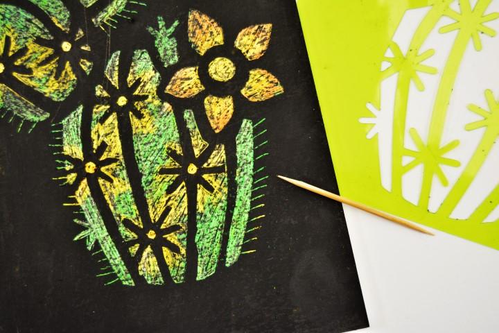 5. Repositionner le pochoir à l'aide des repères et gratter tout le motif du pochoir : les couleurs apparaissent.