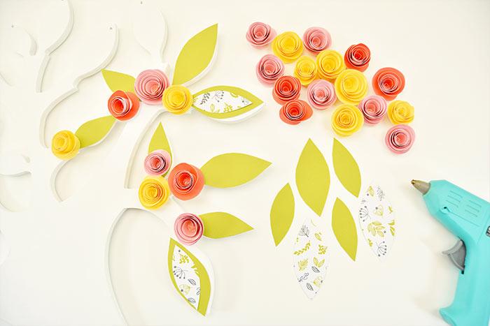5. Coller harmonieusement les feuillages et les fleurs en papier sur l'arbre.