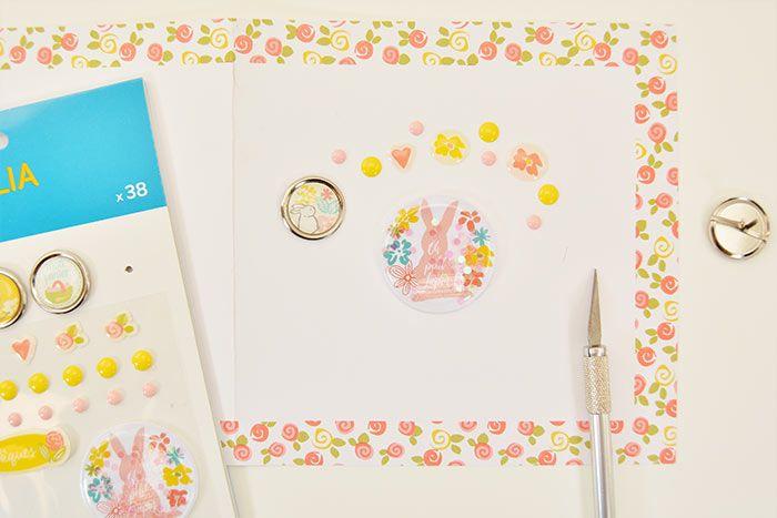 1. Pour former une carte double, plier en deux un papier imprimé 15 x 30 cm de la collection. Coller au centre un sticker de Pâques et former une couronne tout autour avec les différents embellissements de la planche de la collection.