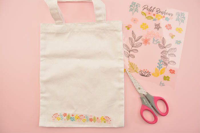1. Repasser le sac en tissu. Découper les motifs choisis dans la planche de thermocollants. Poser un premier motif sur le sac.