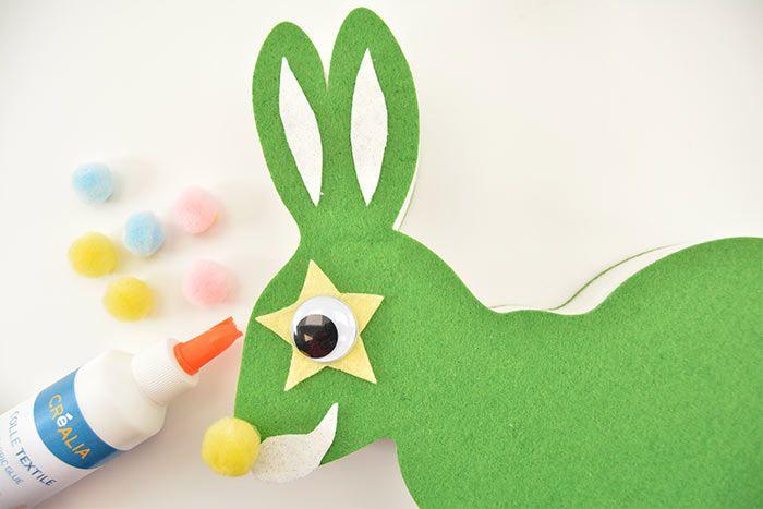 Le Lapin Super-héros-magicien 1. Encoller les éléments du visage et des oreilles sur le lapin et ajouter un pompon coloré pour le museau, au dessus de sa moustache.
